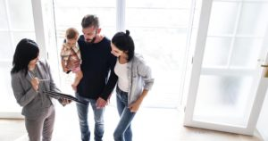Young family looking at documents with a real estate agent