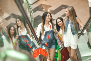 Three friends on an escalator with shopping bags smiling