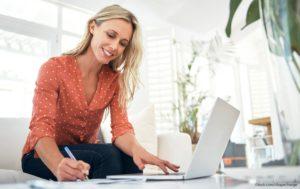 Smiling woman looking at laptop