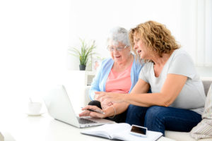 Woman and older woman looking at laptop together