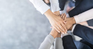 A group of people putting their hands in the middle one on top of the other